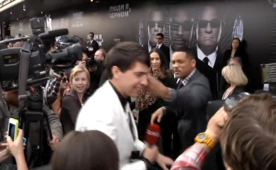 Photo -   In this video image taken from AP video U.S. actor Will Smith, center right, slaps reporter Vitalii Sediuk, white suit, from the Ukrainian television channel 1+1 on the red carpet before the premiere of
