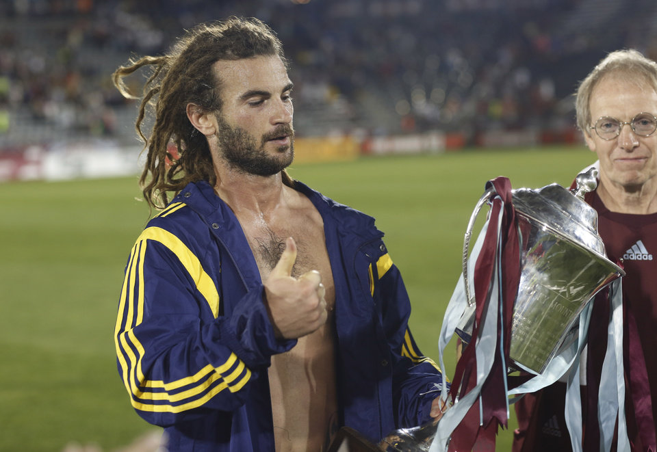 Photo - Real Salt Lake midfielder Kyle Beckerman gestures as he claims the Rocky Mountain Cup after the team's 1-0 victory over the Colorado Rapids in a soccer game in Commerce City, Colo., on Saturday, Aug. 2, 2014. With the win, Real Salt Lake claimed the Rocky Mountain Cup, which is awarded to the winner of the teams' regular-season schedule. (AP Photo/David Zalubowski)
