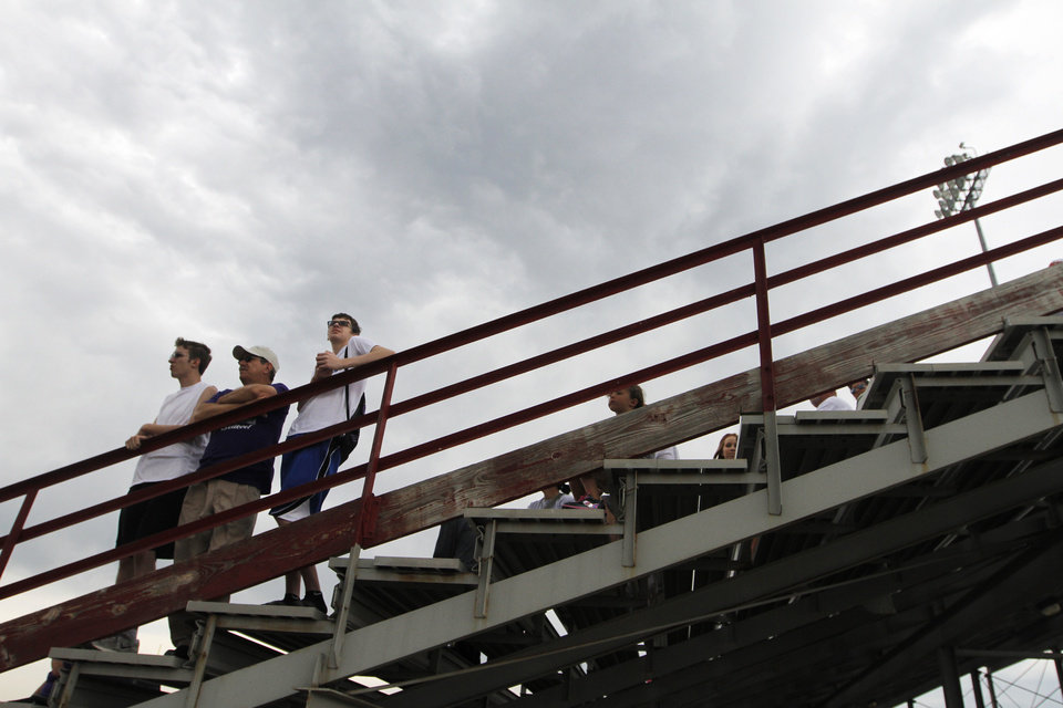 Photo - HIGH SCHOOL TRACK AND FIELD: Fans watch track and field events during a track meet at Carl Albert High School in Midwest City, Friday, May 4, 2012.  Photo by Garett Fisbeck, For The Oklahoman