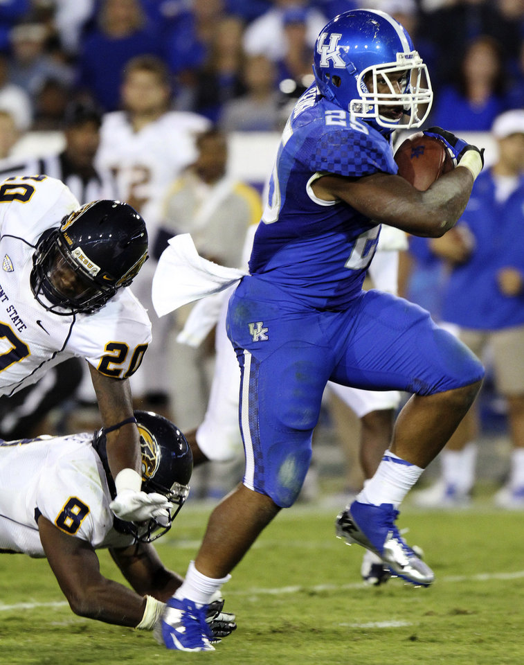 Photo -   Kentucky's Jonathan George, right, eludes Kent State's Malcom Pannell (20) and Calvin Tiggle (8) for a touchdown during the third quarter of an NCAA college football game at Commonwealth Stadium in Lexington, Ky., Saturday, Sept. 8, 2012. Kentucky won 47-14. (AP Photo/James Crisp)
