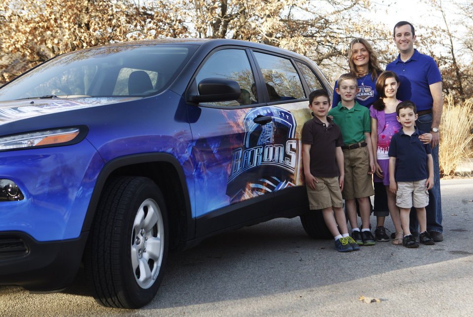 Photo -  Above, right: Linette and Steve England stand behind their children  beside their new Jeep Cherokee. Photo by K.T. King, The Oklahoman   KT King -