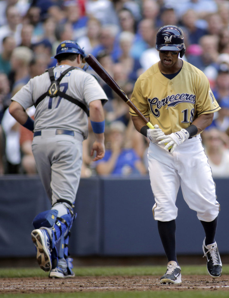 Photo - Milwaukee Brewers' Khris Davis, left, reacts after striking out against the Los Angeles Dodgers during the fourth inning of a baseball game Sunday, Aug. 10, 2014, in Milwaukee. (AP Photo/Darren Hauck)