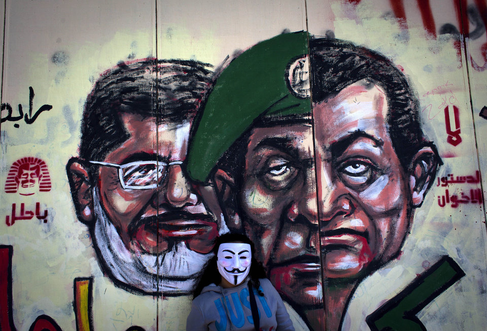 Photo - FILE -In this Saturday, Dec. 8, 2012 file photo, an Egyptian protester wears a Guy Fawkes mask while posing for a photo next to a mural painted overnight on the exterior  wall of the presidential palace depicting president Mohammed Morsi, left, former military council ruler Hussein Tantawi, center and ousted President Mubarak with Arabic that reads