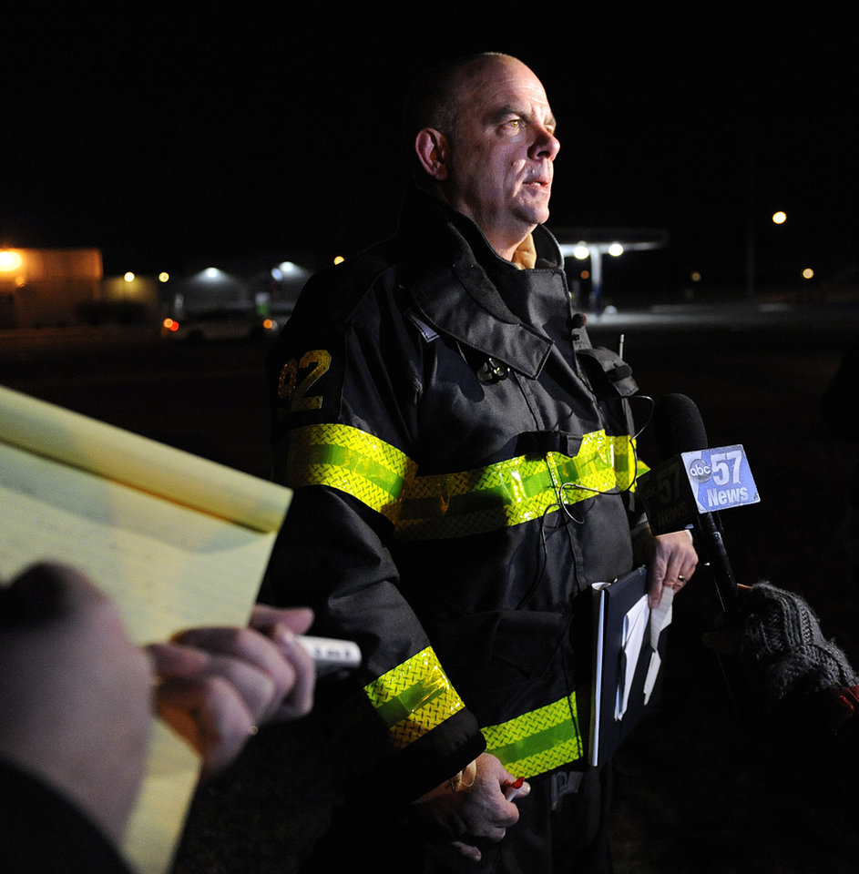 Photo - South Bend Fire Department Assistant Chief John Corthier answers questions about a plane crash that occurred near the South Bend Regional Airport Sunday March 17, 2013 in South Bend, Ind. The private jet apparently experiencing mechanical trouble crashed in a northern Indiana neighborhood, resulting in injuries and striking three homes, authorities and witnesses said. (AP Photo/Joe Raymond)