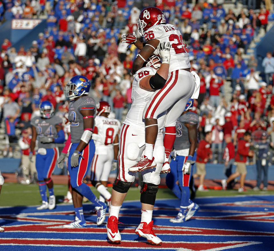 Photo - OU's Damien Williams (26) and Bronson Irwin (68) celebrate a Williams touchdown in the fourth quarter during of the college football game between the University of Oklahoma Sooners (OU) and the University of Kansas Jayhawks (KU) at Memorial Stadium in Lawrence, Kan., Saturday, Oct. 19, 2013. OU won 34-19. Photo by Sarah Phipps, The Oklahoman