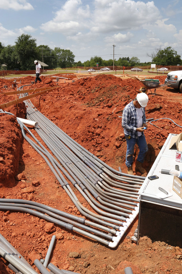 Photo -  Workers lay pipe for Edmond's first splash pad at Barnett Fields at Main Street and Kelly Avenue. The pad is expected to be completed by the end of August. PHOTOs BY PAUL HELLSTERN, THE OKLAHOMAN   PAUL HELLSTERN