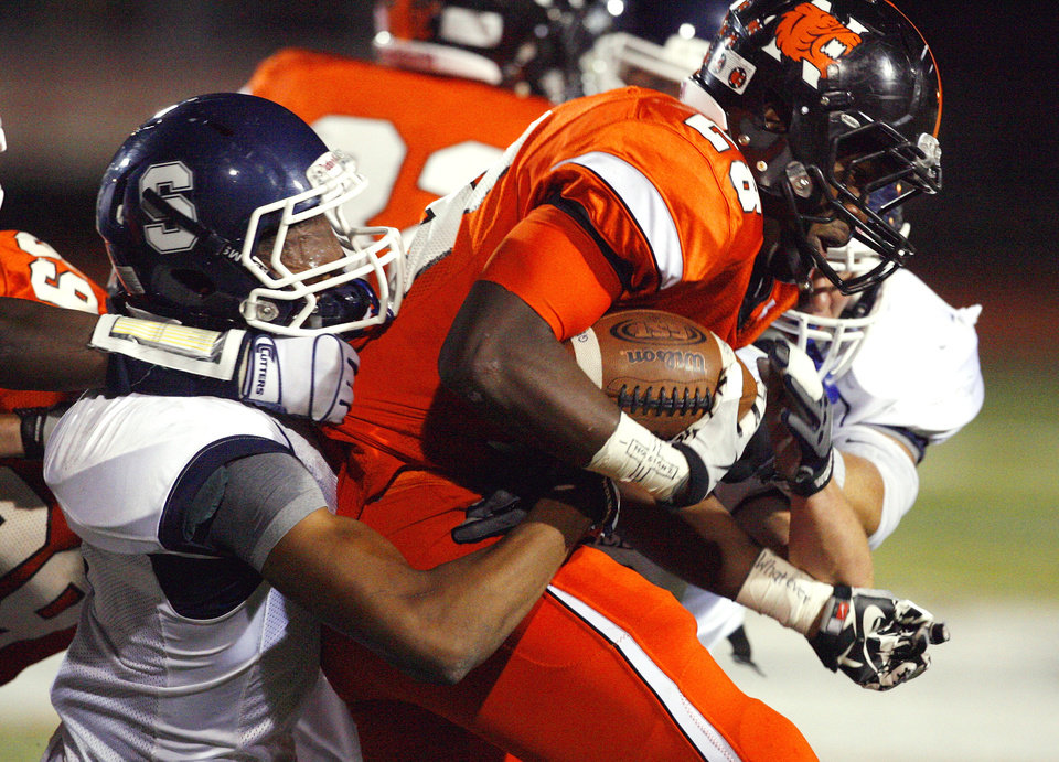 Photo - Tiger Donovan Roberts (28) carries dragging several Shawnee tacklers in high school football at Harve Collins field on Thursday, Sept. 30, 2010, in Norman, Okla.  Photo by Steve Sisney, The Oklahoman