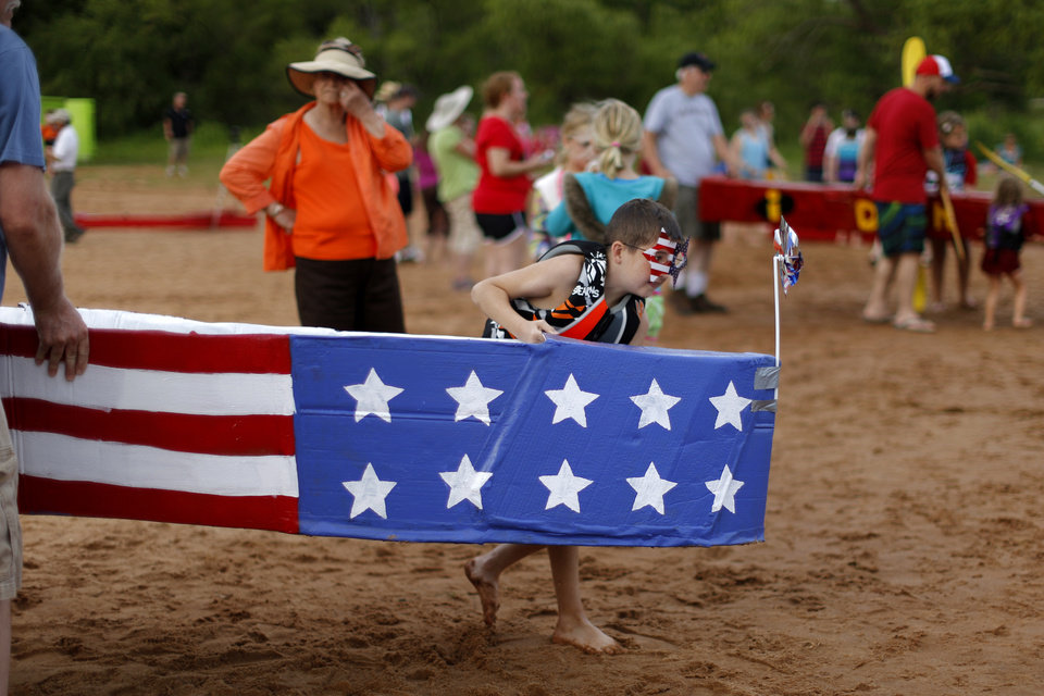 Photo -  Kye Sparks, 9, helps carry Flag Boat before the family's fourth Cardboard Boat Regatta as part of the LibertyFest events at Arcadia Lake. PHOTO BY BRYAN TERRY, THE OKLAHOMAN   Bryan Terry -  THE OKLAHOMAN