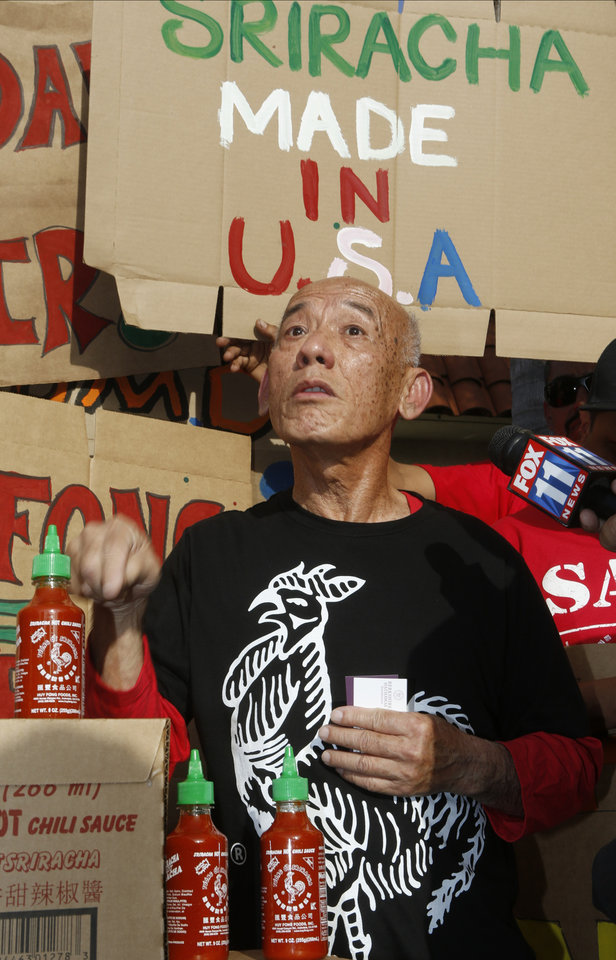Photo - Sriracha hot sauce founder David Tran vows to stay in Irwindale, Calif., as he is joined by supporters protesting ahead of the city council meeting in Irwindale, Calif., Wednesday, April 23, 2014. The Irwindale City Council has declared that the factory that produces the popular Sriracha hot sauce is a public nuisance. (AP Photo/Damian Dovarganes)