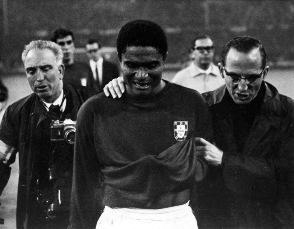 Photo - FILE - In this July 26, 1966 file photo, Portugal's star player Eusebio is led from the pitch in tears after England defeated Portugal 2-1 in the semifinal of the World Cup at Wembley, London. Eusebio, the Portuguese football star who was born into poverty in Africa but became an international sporting icon and was voted one of the 10 best players of all time, has died of heart failure aged 71, Sunday, Jan. 5, 2014. (AP Photo/Bippa, File)
