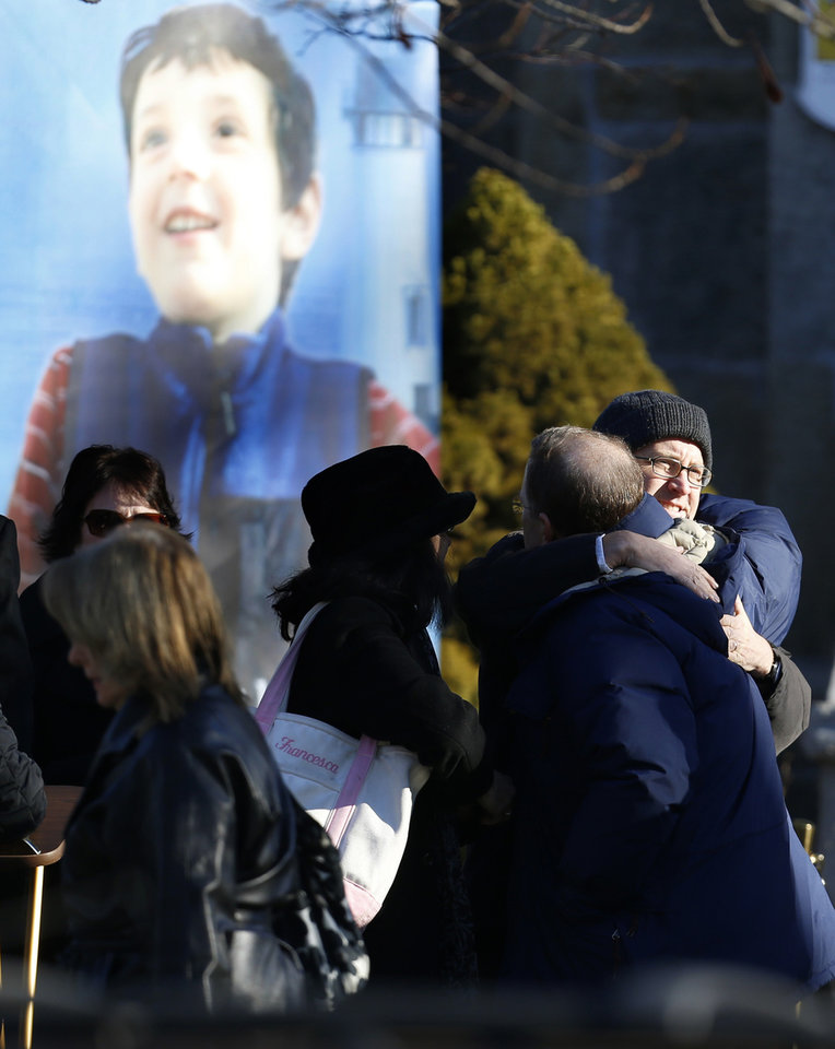 A portrait of Benjamin Andrew Wheeler, one of the students killed in the Sandy Hook Elementary School shooting last week, stands outside of Trinity Episcopal Church as two men embrace each other before his funeral services, Thursday, Dec. 20, 2012, in Newtown, Conn. Wheeler, 6, died when the gunman, Adam Lanza, walked into Sandy Hook Elementary School in Newtown,  Dec. 14, and opened fire, killing 26 people, including 20 children, before killing himself. (AP Photo/Julio Cortez)