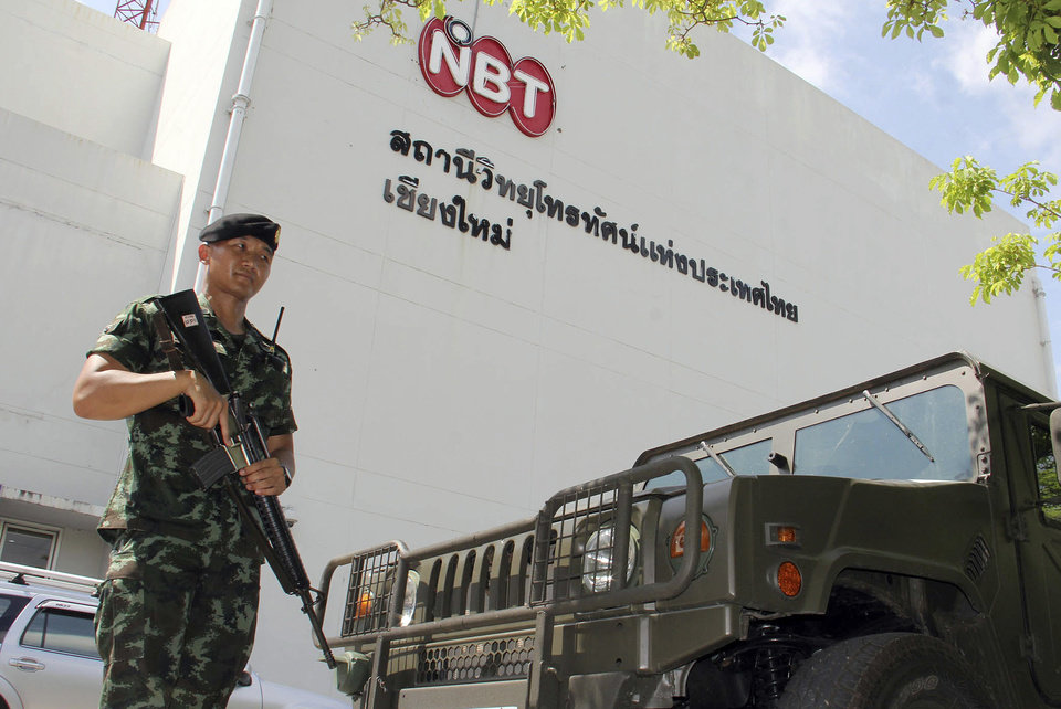 Photo - A Thai soldier stands guard outside a branch of the National Broadcasting Services of Thailand (NBT) Tuesday, May 20, 2014, in Chiang Mai, Thailand. Thailand's army declared martial law in a surprise announcement in Bangkok before dawn on Tuesday, intensifying the turbulent nation's deepening political crisis. The military, however, denied a coup d'etat was underway. (AP Photo/Wichai Taprieu)