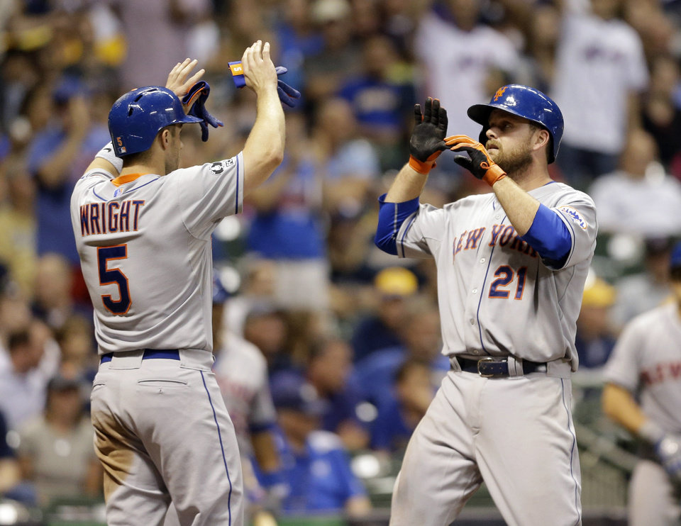 Photo - New York Mets' Lucas Duda (21) gets high-fives from David Wright (5) after Duda's two-run home run against the Milwaukee Brewers during the ninth inning of a baseball game Friday, July 25, 2014, in Milwaukee. (AP Photo/Jeffrey Phelps)