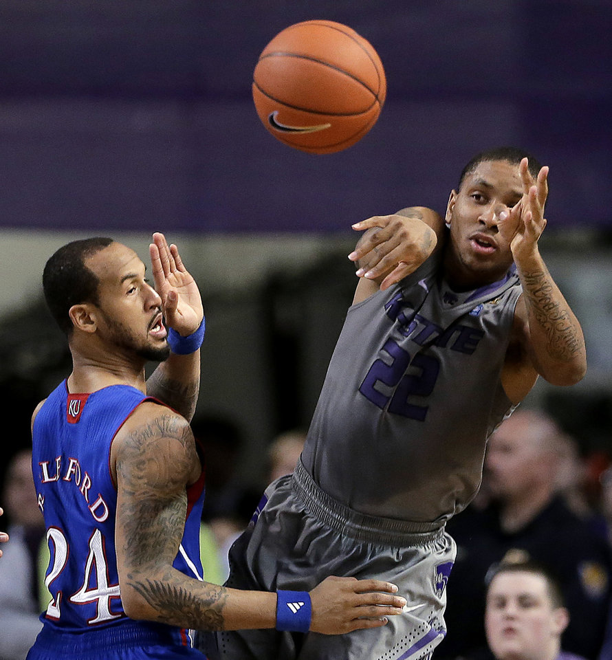 Kansas State guard Rodney McGruder (22) passes around Kansas guard Travis Releford during the first half of an NCAA college basketball game Tuesday, Jan. 22, 2013, in Manhattan, Kan. (AP Photo/Charlie Riedel)