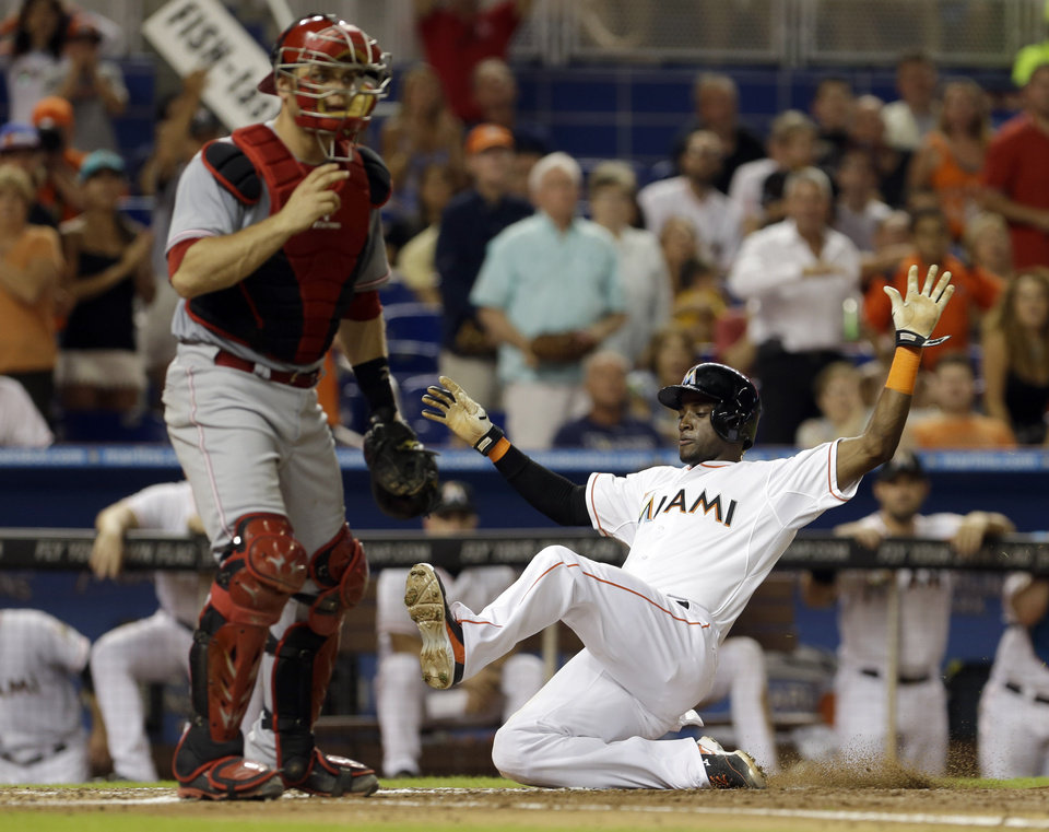 Photo - Miami Marlins' Adeiny Hechavarria, right, slides safely into home plate on a single by Jordany Valdespin as Cincinnati Reds catcher Devin Mesoraco waits for the throw in the fifth inning of a baseball game in Miami, Friday, Aug. 1, 2014. (AP Photo/Alan Diaz)