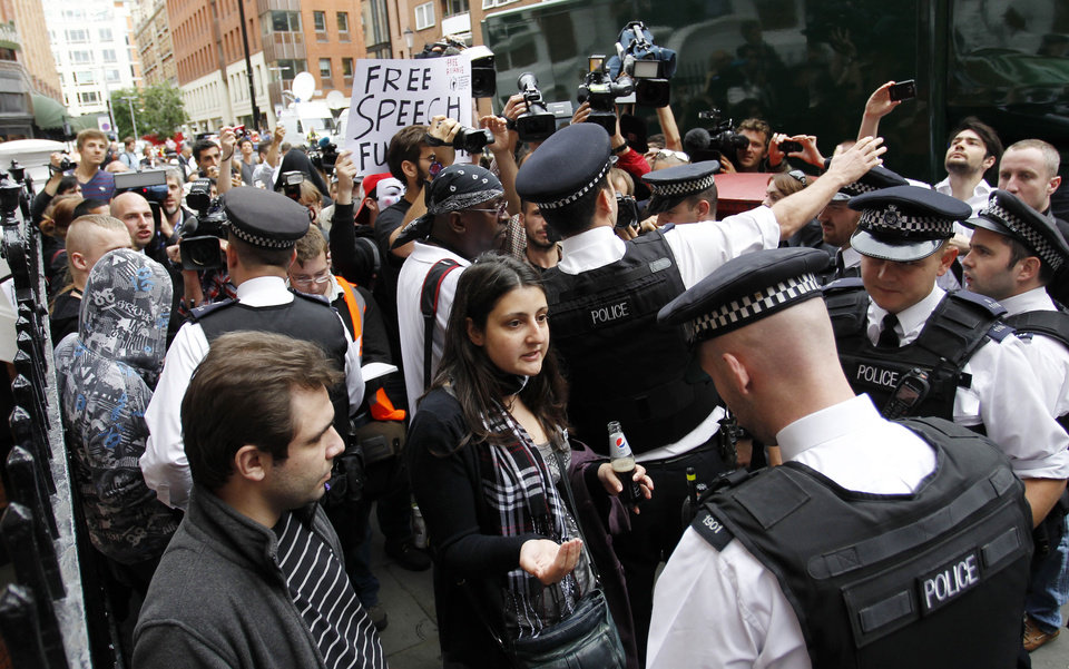 Photo -   British police officers move the protesters in support of WikiLeaks founder Julian Assange from the front of the Ecuadorian Embassy in central London, London, Thursday, Aug. 16, 2012. WikiLeaks founder Julian Assange entered the embassy in June in an attempt to gain political asylum to prevent him from being extradited to Sweden, where he faces allegations of sex crimes, which he denies. (AP Photo/Sang Tan)