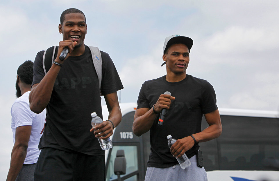 Photo - NBA BASKETBALL: Kevin Durant, left, and Russell Westbrook address fans during a welcome home rally for the Oklahoma City Thunder in a field at Will Rogers World Airport after the team's loss to the Miami Heat in the NBA Finals, Friday, June 22, 2012. Photo by Nate Billings, The Oklahoman