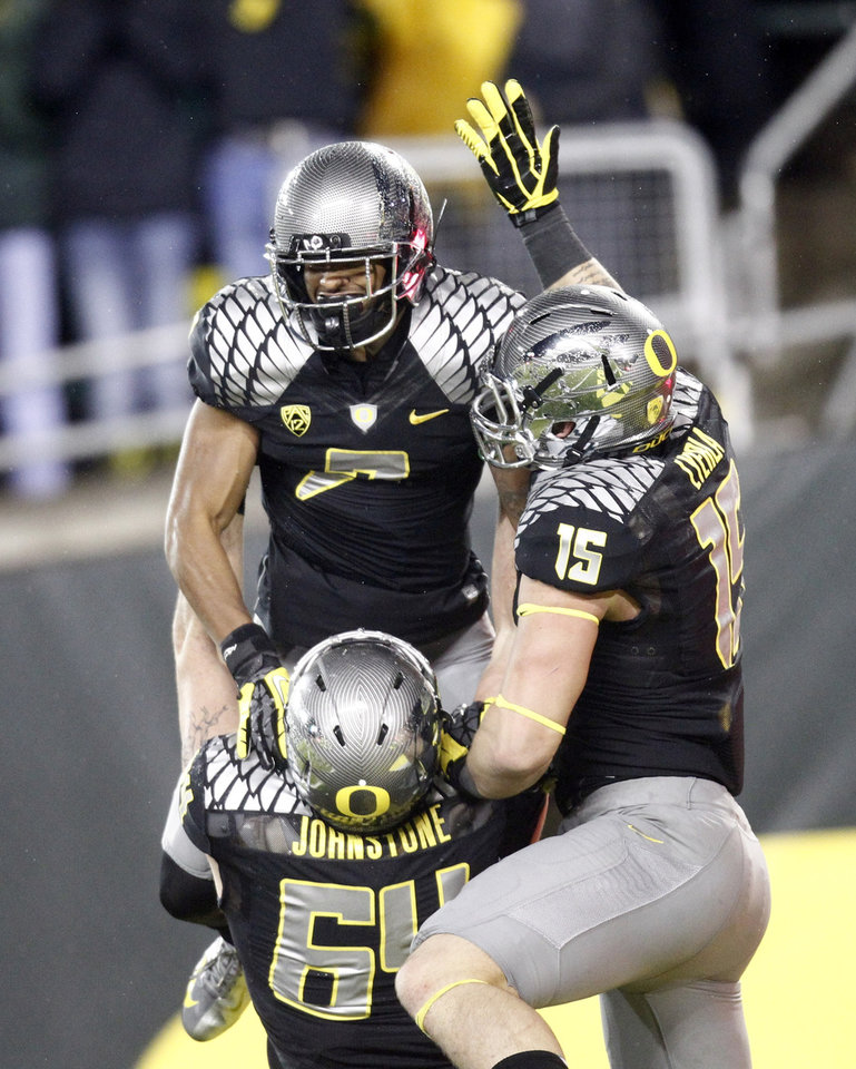 Oregon receiver Keanon Lowe, top left, celebrates his touchdown with teammates Colt Lyerla, right, and Tyler Johnstone during the first half of their NCAA college football game against Stanford in Eugene, Ore., Saturday, Nov. 17, 2012.(AP Photo/Don Ryan)