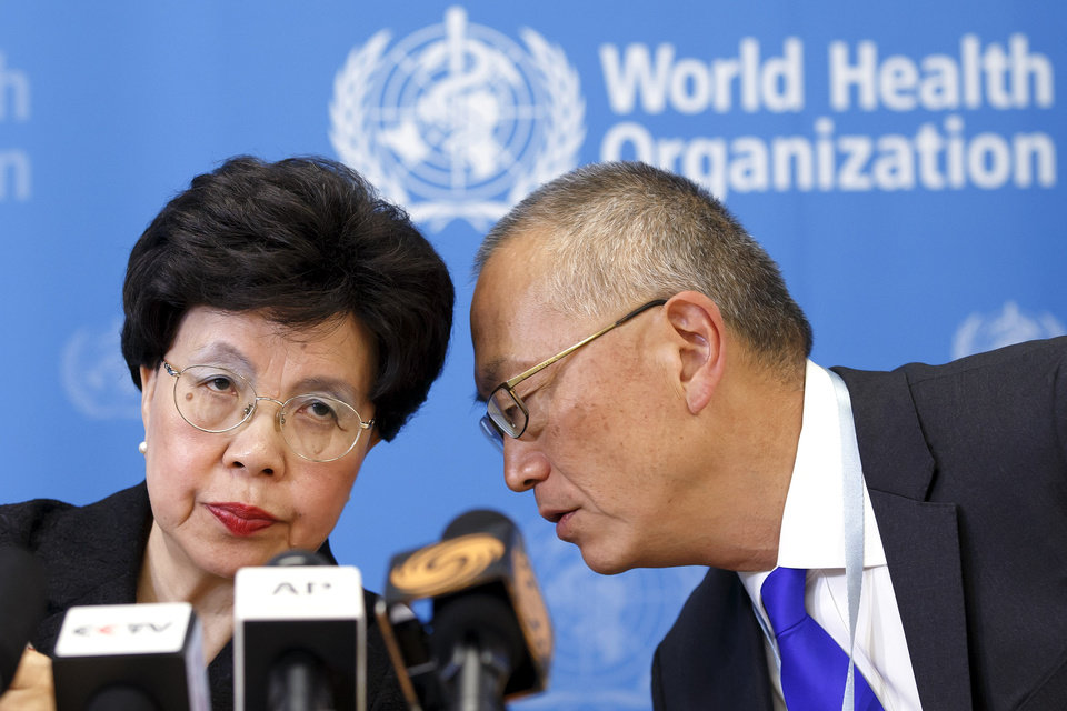 Photo - Director General of the World Health Organization, WHO, China's Margaret Chan and Assistant Director General for Health Security Keiji Fukuda of the US, right, share a word during a press conference after an emergency meeting at the headquarters of the WHO in Geneva, Switzerland, Friday, Aug. 8, 2014. (AP Photo/Keystone, Salvatore Di Nolfi)