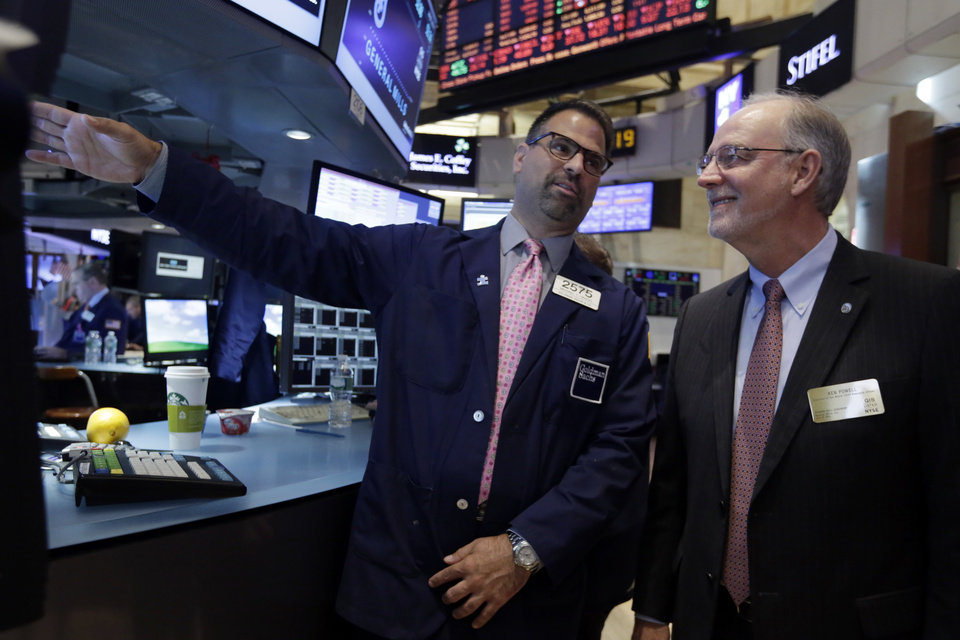 Photo - Specialist Michael Urizzo, left, talks with General Mills Chairman & CEO Kendall Powell as he visits the post that trades his stock on the floor of the New York Stock Exchange, before ringing the opening bell, Tuesday, July 8, 2014. U.S. stocks are opening lower for a second day in a row as investors position themselves for corporate earnings reports. (AP Photo/Richard Drew)