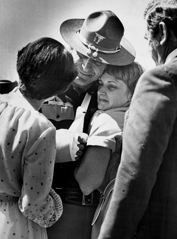 Photo - Oklahoma Highway Patrol Lt. Hoyt Hughes comforts Kay Grimes, widow of slain trooper Lt. Pat Grimes on May 30, 1978. Pat Grimes was one of three troopers killed in a gun battle with two escapees from the Oklahoma State Penitentiary in Caddo on May 26, 1978. Copy of a print from The Oklahoman Archive, Tuesday, Dec. 6, 2011.