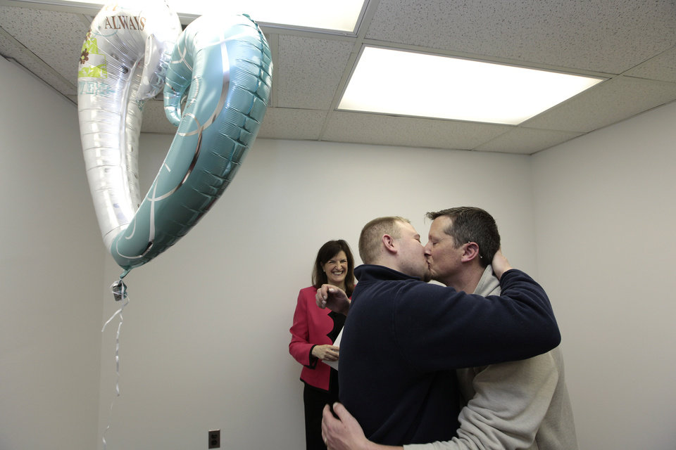 Photo - Justin Flowers, left, and Josh Redder kiss after being married by Oakland County Clerk Lisa Brown at the Oakland County Clerks office in Pontiac, Mich., Saturday, March 22, 2014. A federal judge has struck down Michigan's ban on gay marriage Friday the latest in a series of decisions overturning similar laws across the U.S. Some counties plan to issue marriage licenses to same-sex couples Saturday, less than 24 hours after a judge overturned Michigan's ban on gay marriage. (AP Photo/Paul Sancya)