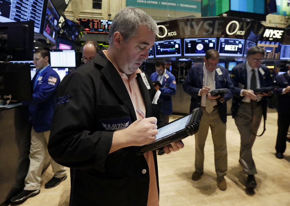 Photo - Trader Edward McCarthy, forground, works on the floor of the New York Stock Exchange, Friday, Oct. 25, 2013. Earnings gains from Microsoft and other big U.S. companies are pushing the stock market higher in early trading. (AP Photo/Richard Drew)