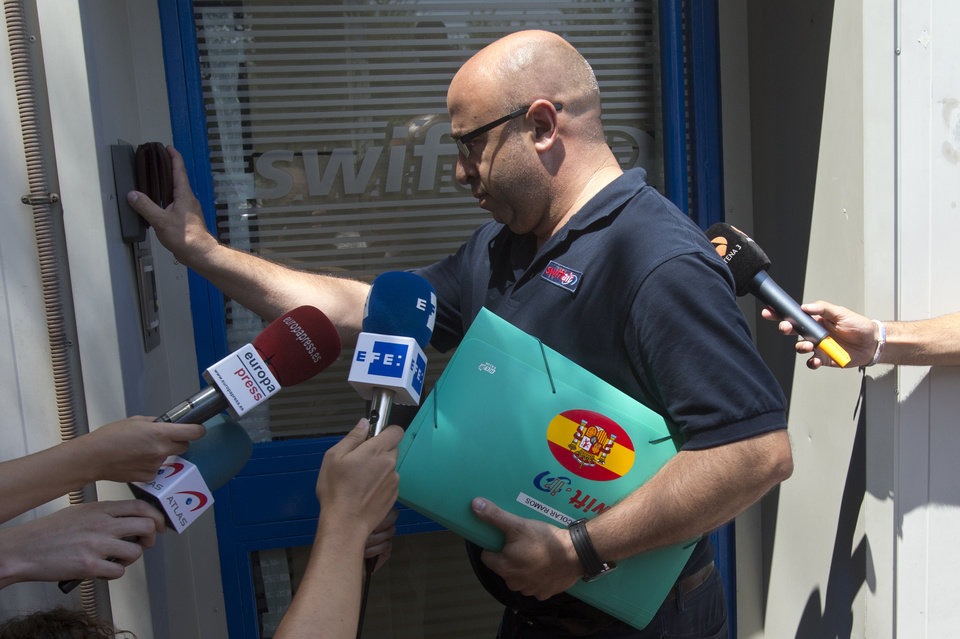 Photo - A man wearing a shirt with a Swiftair logo and carrying a Swiftair folder enters the Spanish airline's office in Madrid, Spain, Thursday, July 24, 2014. An Air Algerie flight carrying 116 people from Burkina Faso to Algeria's capital disappeared from radar early Thursday over northern Mali, officials said. The flight was being operated by Spanish airline Swiftair, the company said in a statement, and the plane belonged to Swiftair. The flight crew was Spanish. (AP Photo/Paul White)
