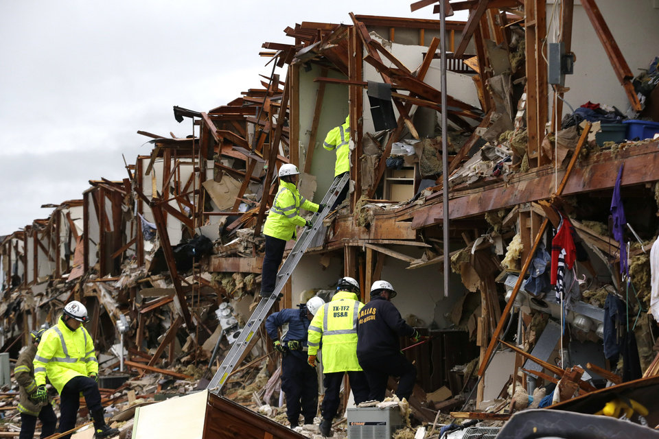 Photo - Firefighters conduct search and rescue of an apartment destroyed by an explosion at a fertilizer plant in West, Texas, Thursday, April 18, 2013.  A massive explosion at the West Fertilizer Co. killed as many as 15 people and injured more than 160, officials said overnight.  (AP Photo/LM Otero)