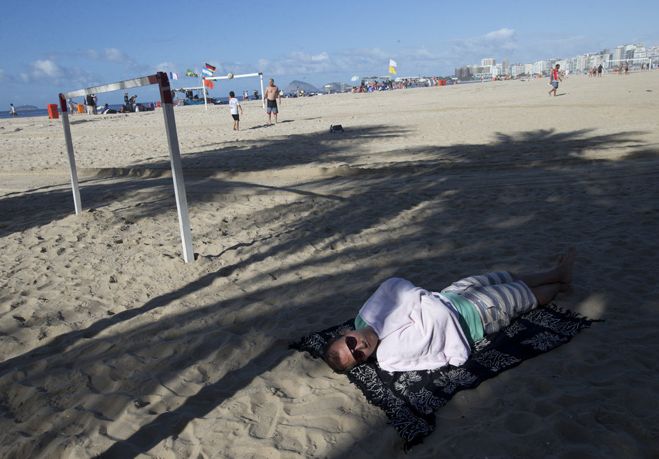 Photo - An Argentina soccer fans sleeps on Copacabana beach the morning of the final World Cup match between Argentina and Germany in Rio de Janeiro, Brazil, Sunday, July 13, 2014. (AP Photo/Silvia Izquierdo)