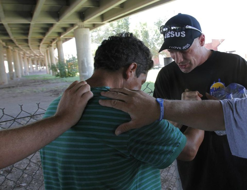 Photo -  HEAT / SUMMER / HOT WEATHER / RELIEF / ASSISTANCE / AID: Scott Sanchez prays over Manuel Garcia, a homeless man, after providing him with water from the City Rescue Mission in Oklahoma City Friday, Aug. 5, 2011.  Photo by Garett Fisbeck, The Oklahoman ORG XMIT: KOD