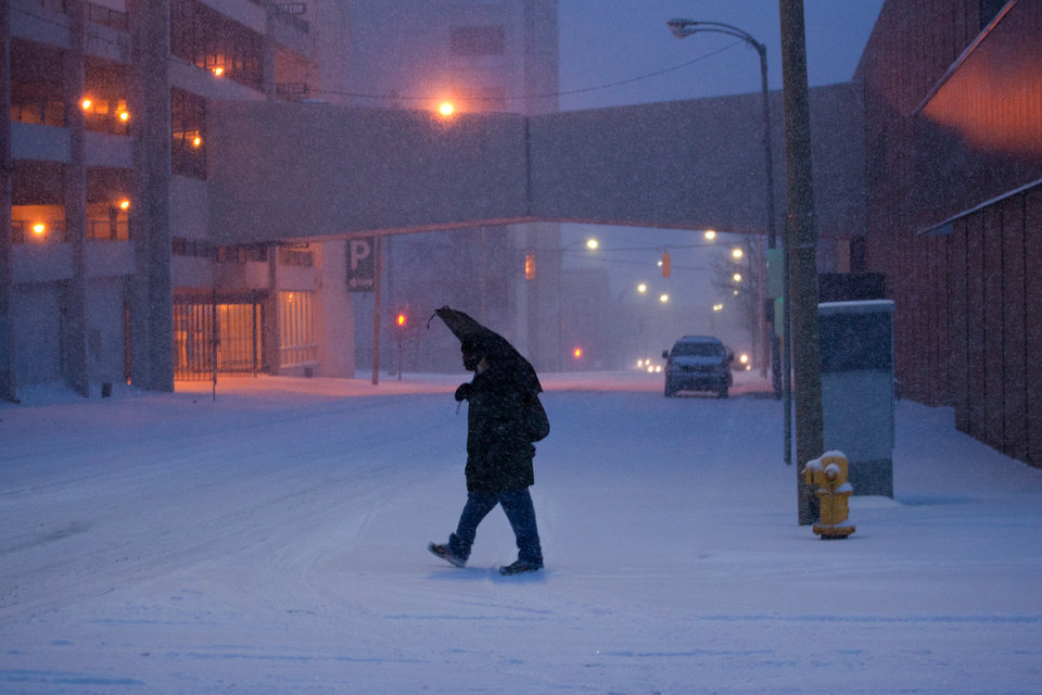 Photo - Charles Crisp makes his way through downtown Flint toward My Brother's Keeper emergency men's shelter, seeking refuge from the snow and cold, on Wednesday, Dec. 26, 2012. Snow began falling around 3pm in Genesee County and a winter weather advisory is in effect until 7am Thursday. Up to four inches of snowfall is expected in the area. (AP Photo/The Flint Journal, Griffin Moores) LOCAL TV OUT; LOCAL INTERNET OUT