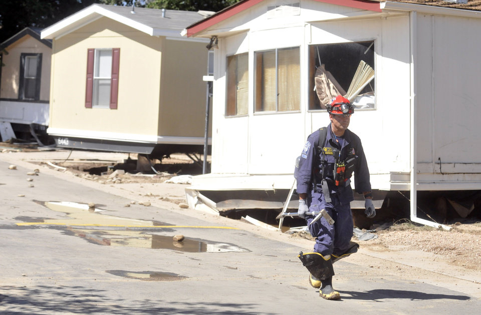 Photo - A search and rescue member walks by the homes that other FEMA officials checked earlier that day during FEMA's sweep through the neighborhood Sept. 18, 2013 along 37th Street in Evans, Colo. (AP Photo/The Greeley Tribune, Joshua Polson)