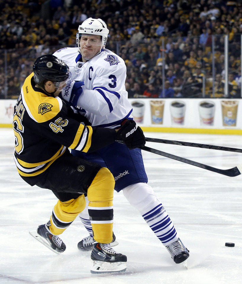 Photo - Toronto Maple Leafs defenseman Dion Phaneuf (3) keeps Boston Bruins center David Krejci (46) away from the puck in the second period of an NHL hockey game in Boston, Tuesday, Jan. 14, 2014. (AP Photo/Elise Amendola)