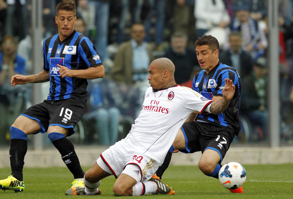 Photo - AC Milan's Nigel De Jong, center, of the Netherlands, fights for the ball with Atalanta's Carlos Carmona, right, of Chile, as Atalanta's German Denis, left, of Argentina, during a Serie A soccer match in Bergamo, Italy, Sunday, May 11, 2014. (AP Photo/Felice Calabro')