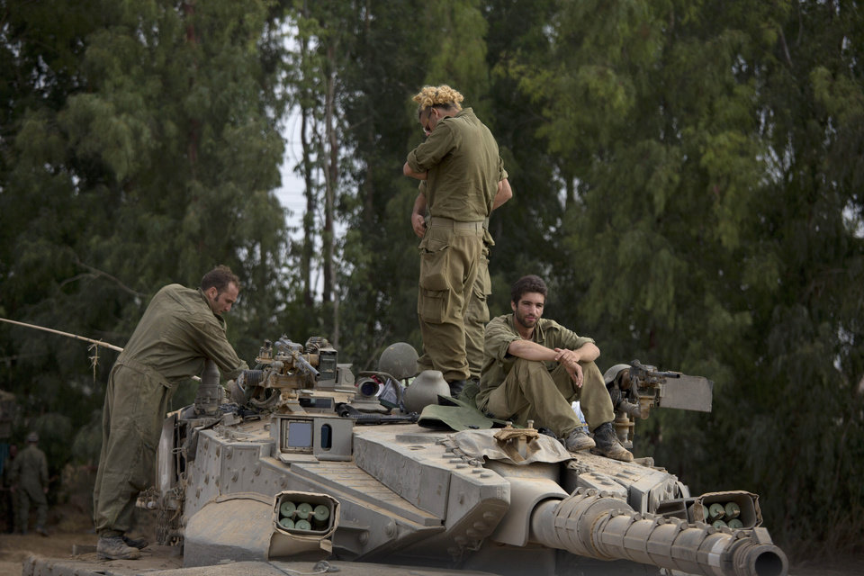 Photo - Israeli soldiers work on a tank near the Israel and Gaza border Thursday, July 24, 2014. Israeli tanks and warplanes bombarded the Gaza Strip on Thursday, as Hamas militants stuck to their demand for the lifting of an Israeli and Egyptian blockade in the face of U.S. efforts to reach a cease-fire. (AP Photo/Dusan Vranic)