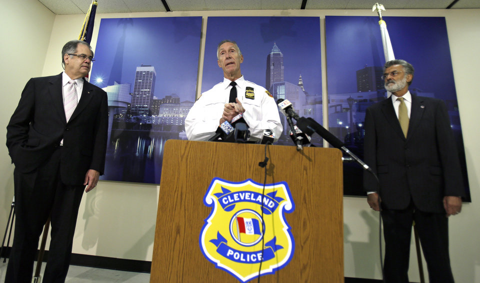 Photo - Cleveland Police Chief Michael McGrath, center, announces the results of disciplinary hearings for officers involved in a deadly chase Tuesday, Oct. 15, 2013, in Cleveland. McGrath said 63 officers have been suspended for breaking rules during a deadly chase last November. McGrath says the longest suspension handed down was 10 days. Director of Public Safety Martin L. Flask, left, and Cleveland Mayor Frank Jackson, right, listen. (AP Photo/Tony Dejak)