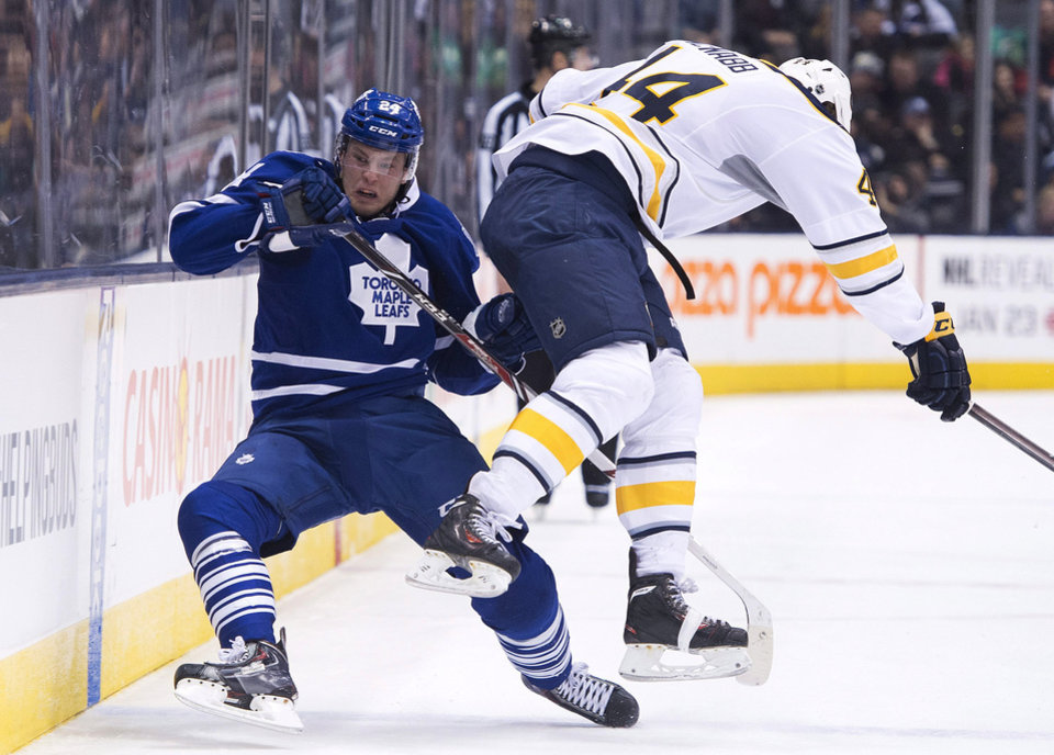 Photo - Toronto Maple Leafs forward Peter Holland, left, gets taken out by Buffalo Sabres defenseman Brayden McNabb, right, during the second period of an NHL hockey game, Wednesday, Jan. 15, 2014 in Toronto. (AP Photo/The Canadian Press, Nathan Denette)