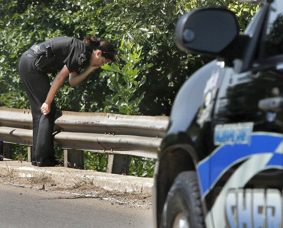 An Oklahoma County Sheriff\'s deputy leans over the bridge railing to look at partially submerged car in the ravine below. The body of a missing Kingfisher woman was found inside her vehicle lodged beneath a bridge in a heavily wooded area on Council Road about a quarter-mile south of NW 178 Street in Oklahoma City, relatives said. Simon\'s granddaughter, Aaron Harbin, said Simon\'s 2004 Buick LeSabre was found upside down in a ravine Saturday morning, June 30, 2012. Searchers noticed her car about 10:30 a.m. as they were walking a two-mile grid along Council Road as part of a team of nearly 100 volunteers who looked for Simon or her car this morning. She was reported missing on June 20. Photo by Jim Beckel, The Oklahoman