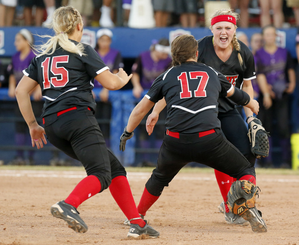 From left, Grove\'s Mason Jeffries (15), Taylor Dodson (17) and Jessica Walker (19) celebrate after wining the 5A state championship fast-pitch softball game against Chickasha at ASA Hall of Fame Stadium in Oklahoma City, Monday, Oct. 15, 2012. Grove won, 3-2. Photo by Nate Billings, The Oklahoman