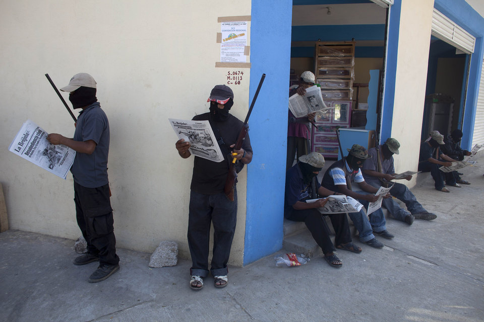 In this photo taken Friday Jan. 18, 2013, masked and armed men read newspapers as they stand guard at the entrance to the town of Ayutla, Mexico. Hundreds of men have taken up arms in several towns of the southern state of Guerrero to defend their communities against violent criminal gangs. (AP Photo/Dario Lopez-Mills)