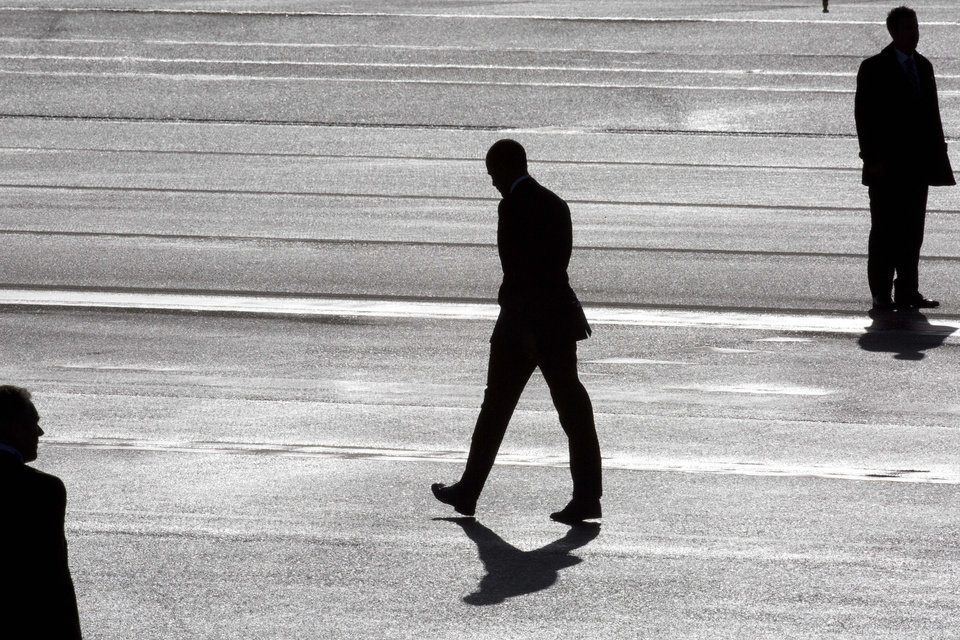 Photo - President Barack Obama, center, and two secret service agents are silhouetted as he walks towards Marine One helicopter upon arrival at Schiphol Amsterdam Airport, Netherlands, Monday March 24, 2014. Obama will attend the two-day Nuclear Security Summit in The Hague. (AP Photo/Peter Dejong, POOL)