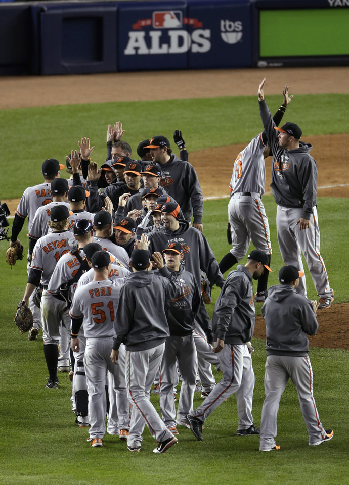 Photo -   The Baltimore Orioles celebrate after beating the New York Yankees 2-1 in 13 innings in Game 4 of the American League division baseball series Thursday, Oct. 11, 2012, in New York. (AP Photo/Peter Morgan)