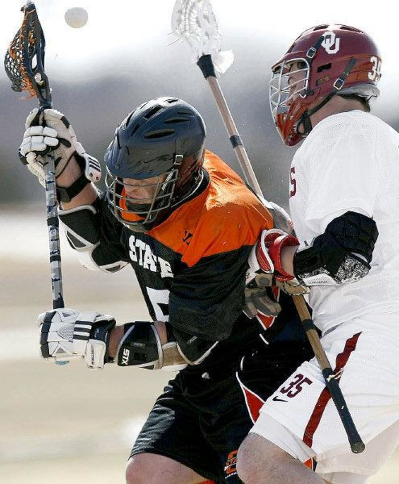 The ball pops free as the Univesrity of Oklahoma's Chris Hodgson and Oklahoma State University's R.J. Butler collide during a Bedlam lacrosse game Sunday in Edmond. PHOTO BY JOHN CLANTON, THE OKLAHOMAN.  <strong>John Clanton</strong>