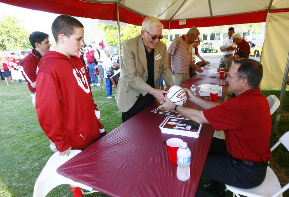 Photo - OU basketball coach Lon Kruger (right) signs a basketball for Ron McDaniel (center) and his grandson Coleman McDaniel (left) during the Sooner Caravan at OU-Tulsa on Monday, May 6, 2013. MATT BARNARD/Tulsa World ORG XMIT: DTI1305062004301127