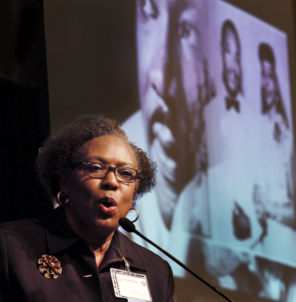 Photo - Images of Martin Luther King are projected on a screen behind her as Joyce Jackson, mistress of ceremonies, introduces a speaker during the 16th annual Midwest City Dr. Martin Luther King, Jr. Prayer Breakfast inside the Reed Conference Center Monday morning, Jan. 21, 2013. Jackson is also the MLK Prayer Breakfast committee chairperson. The theme of this year's event is