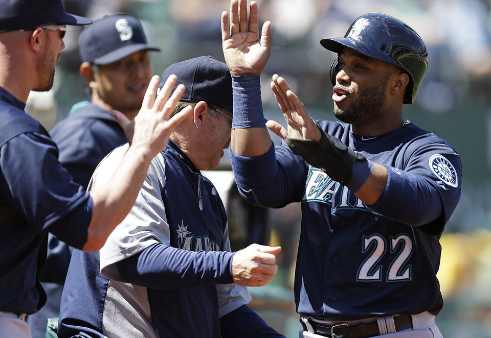 Photo - Seattle Mariners' Robinson Cano is congratulated after scoring against the Oakland Athletics in the third inning of a baseball game Sunday, April 6, 2014, in Oakland, Calif. Cano scored on a single by Justin Smoak. (AP Photo/Ben Margot)