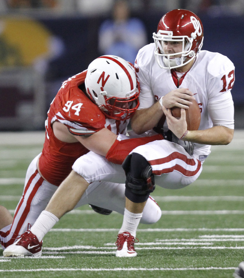 Photo - Oklahoma's Landry Jones (12) is sacked by Nebraska's Jared Crick (94) during the Big 12 football championship game between the University of Oklahoma Sooners (OU) and the University of Nebraska Cornhuskers (NU) at Cowboys Stadium on Saturday, Dec. 4, 2010, in Arlington, Texas.  Photo by Chris Landsberger, The Oklahoman