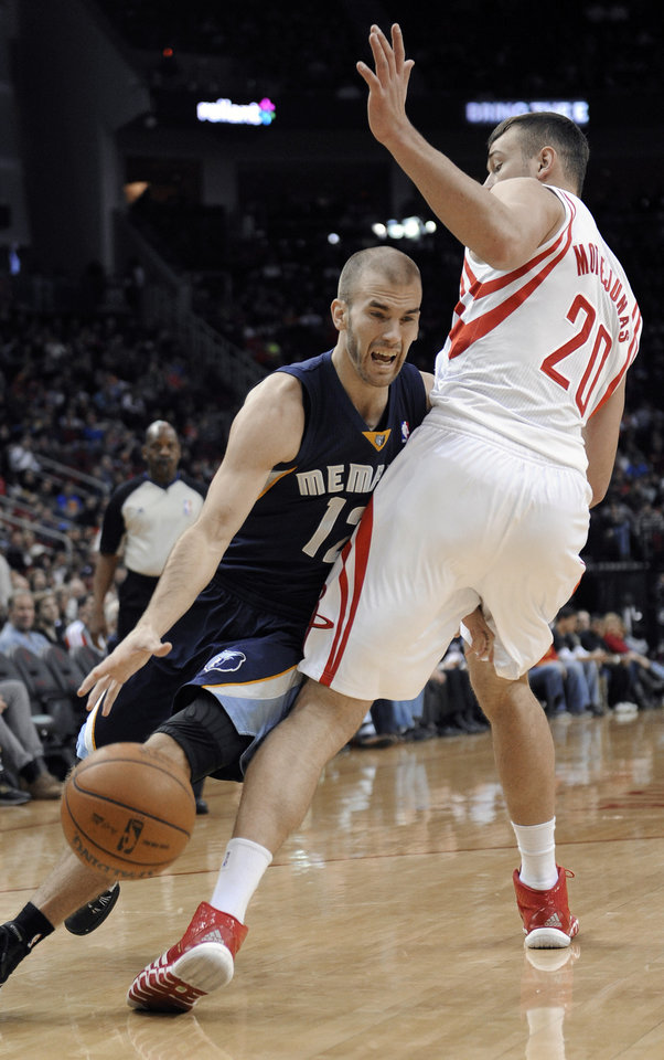 Photo - Memphis Grizzlies' Nick Calathes (12) drives the ball around Houston Rockets' Donatas Motiejunas (20) during the first half of an NBA basketball game Friday, Jan. 24, 2014, in Houston. (AP Photo/Pat Sullivan)
