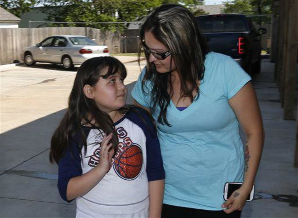 Jazmin Rodriguez, left, looks up at her mother, LaTisha Garcia, right, following an interview in Moore, Okla., Thursday, May 23, 2013. Garcia carried her injured daughter away from a school that was hit by a tornado on Sunday. (AP Photo/Sue Ogrocki)